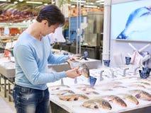 Man chooses carp fish in supermarket Royalty Free Stock Image