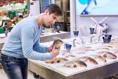 Man chooses carp fish in supermarket Stock Photography
