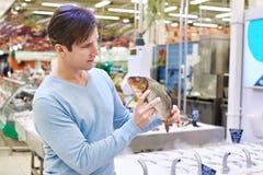 Man chooses carp fish in supermarket Stock Image