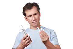 Man chooses changeable head for electric toothbrush Stock Image