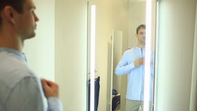 A man chooses clothes for himself in a clothing store. Trying on new clothes in the fitting room stock video footage