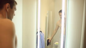 A man chooses clothes for himself in a clothing store. Trying on new clothes in the fitting room stock footage