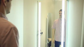 A man chooses clothes for himself in a clothing store. Trying on new clothes in the fitting room stock video