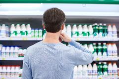 Man chooses dairy products in store Royalty Free Stock Photos