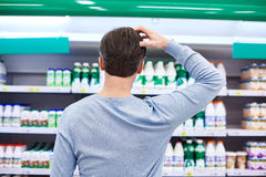 Man chooses dairy products in store Royalty Free Stock Images