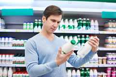 Man chooses dairy products in store. Man chooses dairy products in the store Royalty Free Stock Photo