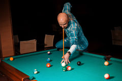 Man chooses a difficult hit on pool billiards Stock Photo