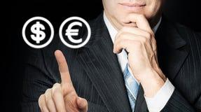 Man chooses between dollar and euro.  stock image