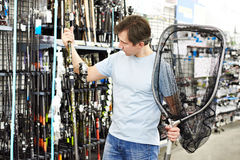 Man chooses fishing rod and landing net in sports shop Royalty Free Stock Photos