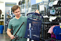 Man chooses fishing rod and net for fish in shop Royalty Free Stock Image