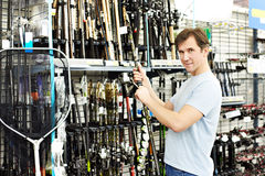Man chooses fishing rod in sports shop Stock Photos