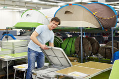 Man chooses folding camp table in store leisure goods Royalty Free Stock Photos