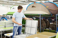 Man chooses folding camp table in store leisure goods Stock Image