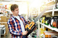 Man chooses gasoline saw royalty free stock photo