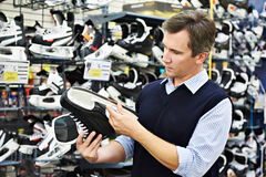 Man chooses hockey skates in sports shop Stock Photos