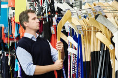Man chooses hockey stick in sports shop Stock Photos