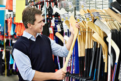 Man chooses hockey stick in sports shop Stock Photography