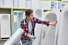 Man chooses home bath in building store Royalty Free Stock Photography