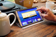 Man chooses hotel through the application Booking on a Tablet PC Royalty Free Stock Photo