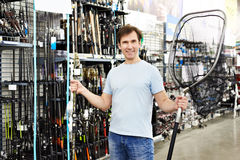 Man chooses landing net for fishing in sports shop Royalty Free Stock Photography