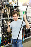 Man chooses landing net for fishing in sports shop Stock Photo