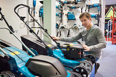 Man chooses lawn mower in store Stock Photos