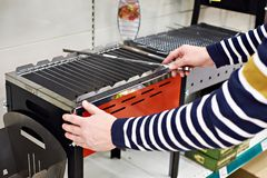 Man chooses mangal barbecue for picnic in store. Man chooses a mangal barbecue for a picnic in the store Stock Image