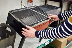 Man chooses mangal barbecue for picnic in store. Man chooses a mangal barbecue for a picnic in the store Royalty Free Stock Images