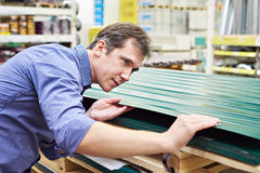 Man chooses metal profile for fence in store Stock Photography