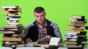 Man chooses the most interesting book, and writes in a notebook. Green screen stock video footage