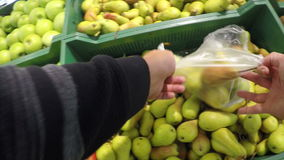 Man chooses pear apples bought in the store the stock footage