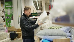 Man chooses pillow in a shop. Bed linen shop.  stock footage