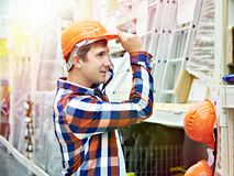 Man chooses a protective helmet in store royalty free stock photos