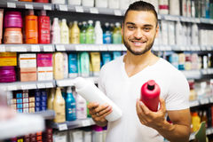 Man chooses shampoo in store Royalty Free Stock Images