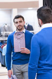 Man chooses a shirt  in a boutique. Stock Images