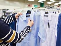Man chooses shirt in shop. Man buyer chooses shirt in shop royalty free stock photos