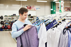 Man chooses a shirt in shop Royalty Free Stock Photo