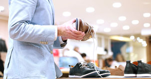 Man Chooses Shoes At Shoe Store Royalty Free Stock Photos
