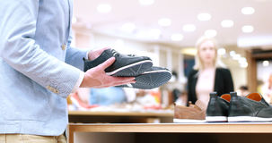 Man Chooses Shoes At Shoe Store Stock Photo