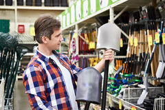 Man chooses shovel in shop to work in garden Stock Images