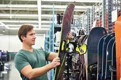 Man chooses snowboard in sport store Stock Images