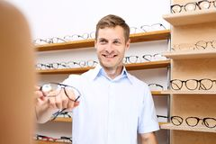 Selection of spectacle frames. The man chooses spectacle frames in the optical salon Royalty Free Stock Image