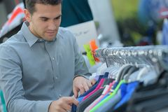Man chooses t-shirt in store stock photos