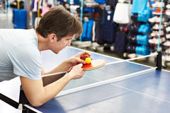 Man chooses table tennis racquet in shop Stock Image