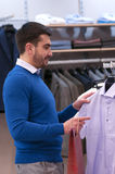 Man chooses tee - shirt at a shop. Attractive young  man chooses tee - shirt at a shop Stock Image