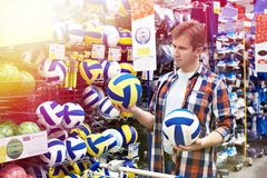 Man chooses volleyball in sports shop Stock Images