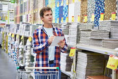 Man chooses wall tiles for bathroom in supermarket building mate Stock Photos
