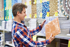 Man chooses wall tiles for bathroom in supermarket building mate Stock Photo
