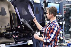 Man chooses wetsuit and fins for spearfishing in sports shop. Man chooses a wetsuit and fins for spearfishing in a sports shop Royalty Free Stock Photos