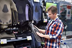 Man chooses wetsuit and fins for spearfishing in sports shop. Man chooses a wetsuit and fins for spearfishing in a sports shop Royalty Free Stock Images